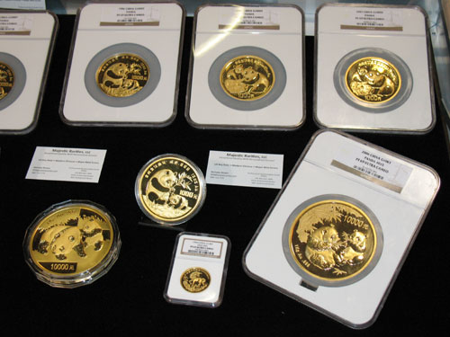 A one-ounce Chinese gold coin is dwarfed by larger gold pieces including a one-kilo coin at the Majestic Rarities table during the February 2009 Long Beach Expo. A much larger display is planned for the upcoming ANA convention in Los Angeles. Photo by Donn Pearlman