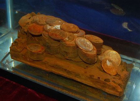 The remains of a wooden cargo box with approximately 110 gold coins as they were found on the ocean floor. (Photo credit: Monaco Rare Coins)