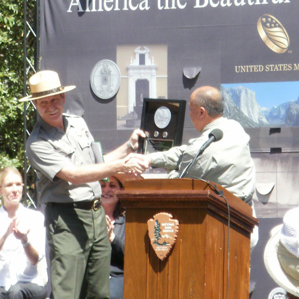 Edmund Moy hands Yosemite National Park Quarter Plaque to Don Neubacher.
