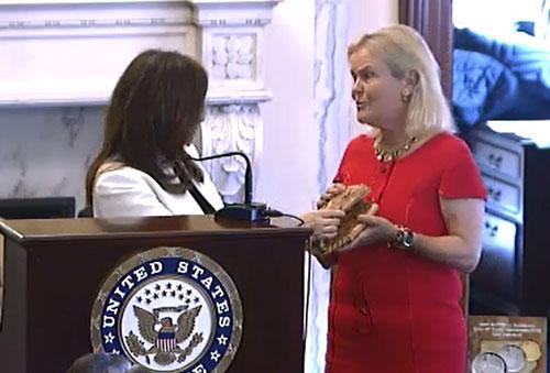 Treasurer Rosie Rios presents Cassie MacFarland's glove to a