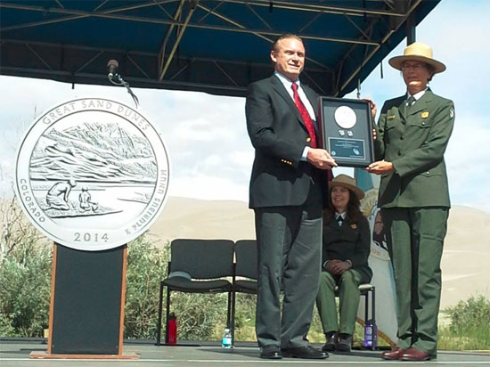 Dave Croft presents first-day production quarters to park superintendent Lisa Carrico. — at Great Sand Dunes National Park and Preserve. United States Mint photo.