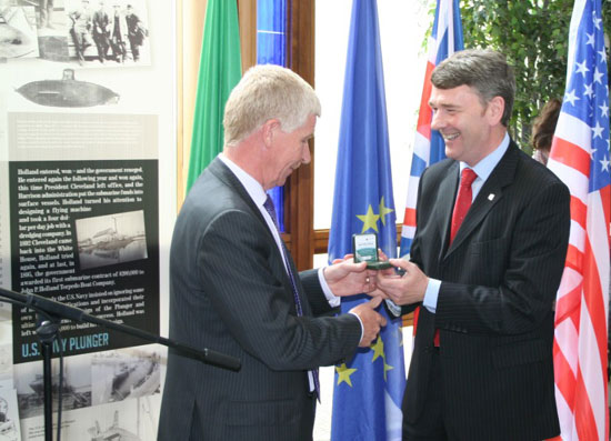Mr. Paul Molumby presents Dr. Heffernan with the series' first strike coin during the launch.