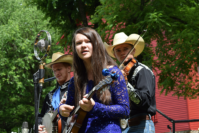 The Baker Family bluegrass band. Banjo and fiddle player in cowboy hats behind female singer with guitar. Mill in background.