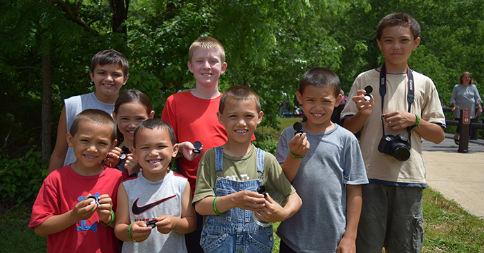 Eight kids, boys and girls of many ethnic backgrounds, proudly hold their new Ozark National Scenic Riverways quarters after the launch ceremony on June 5, 2017.