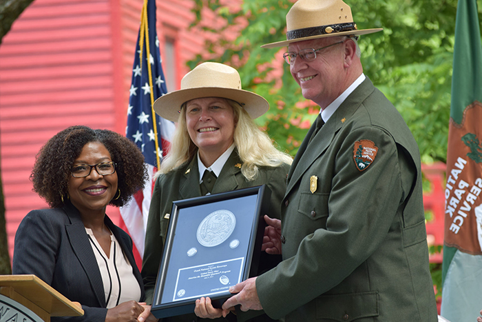 Michele Satchell, senior advisor, Office of Director, U.S. Mint, presenting Ozark National Scenic Riverways quarters struck on the first day of production to National Park Service deputy regional director, Patty Trap, and park superintendent Larry Johnson. Mill and U.S. flag in the background.